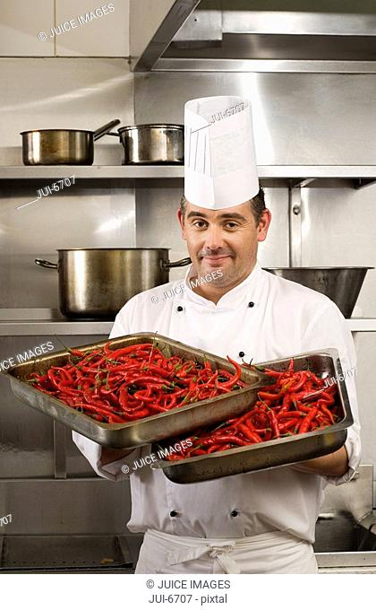 Male chef carrying two full trays of red chilli peppers in commercial kitchen, smiling, portrait