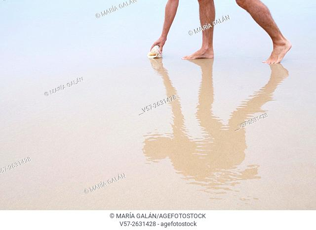 Man on wet sand picking up a shell and its reflection on it