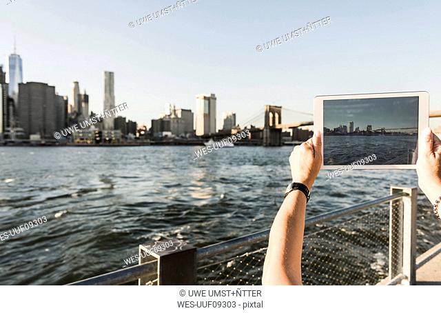 USA, Brooklyn, woman taking picture of Manhattan skyline with tablet, close-up