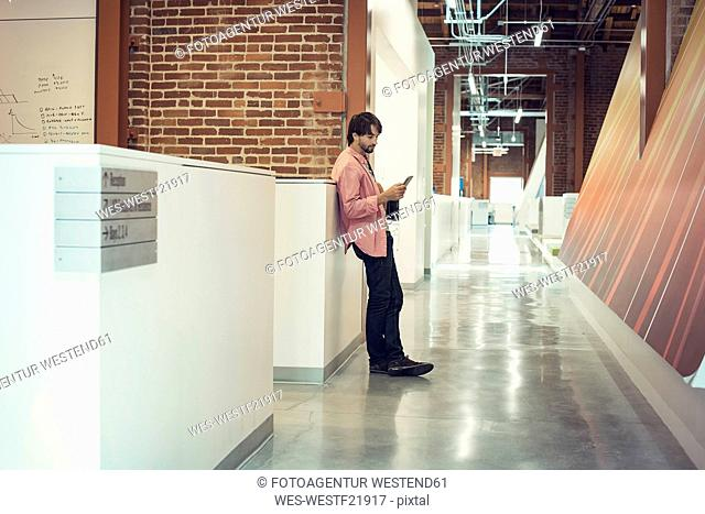 Businessman standing corridor reading messages