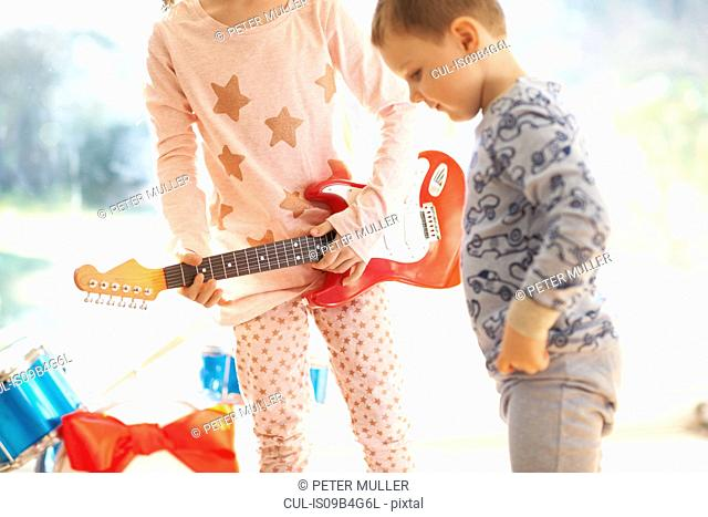 Girl and brother playing with toy guitar on christmas day