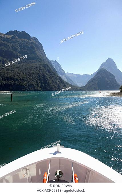 The bow of a tour boat on Milford Sound in front of Mitre Peak in Fiordland National Park, New Zealand
