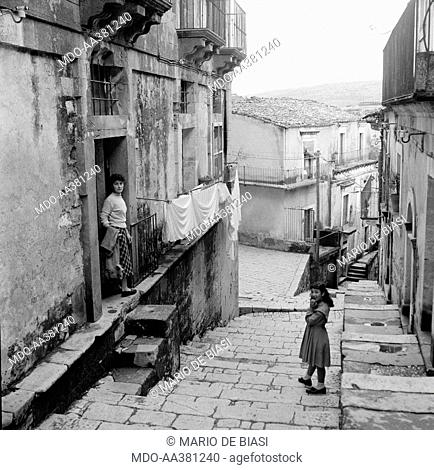 The neighbourhood called Ragusa Ibla. A little girl and a woman standing on the entrance of their house in the neighbourhood called Ragusa Ibla