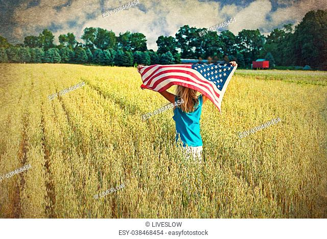 Young girl running with American flag in a wheat field