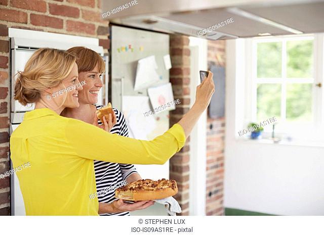Women taking selfie in kitchen with cake