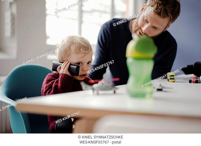 Father watching son, learning how to use a telephone