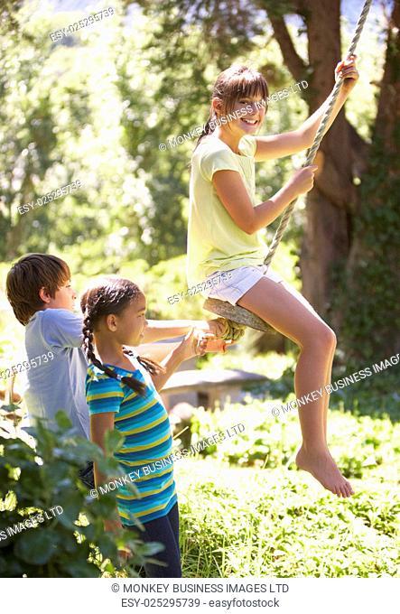 Group Of Friends Having Fun On Rope Swing