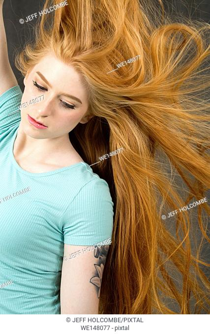 Young woman with long red hair, in green dress, with hair blowing out to side while looking down