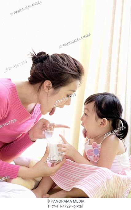 Mother and daughter holding a glass of milk behind in bed