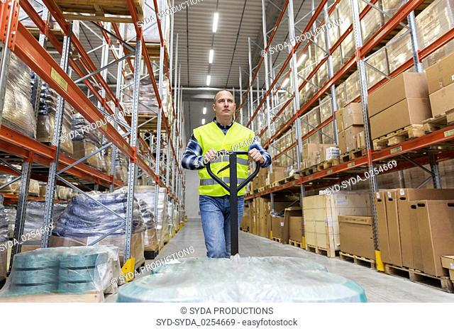 warehouse worker carrying loader with goods