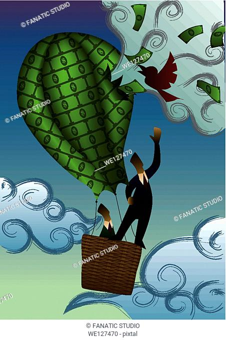 Two businessmen in a hot air balloon of money being burst by a bird
