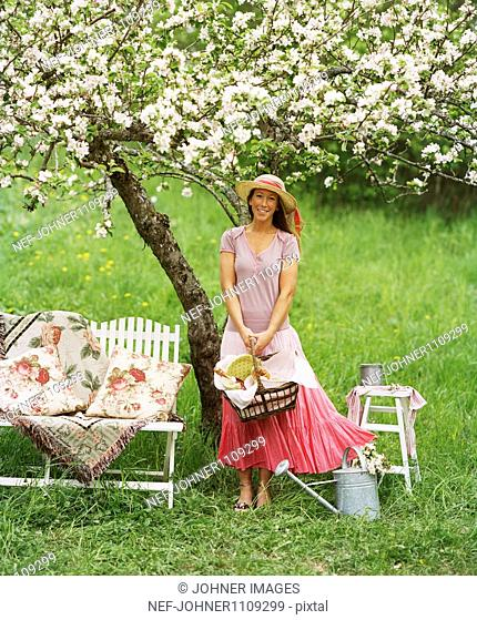 Portrait of woman holding basket above blossoming tree