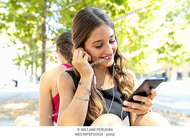 Two young women together at park listening to music
