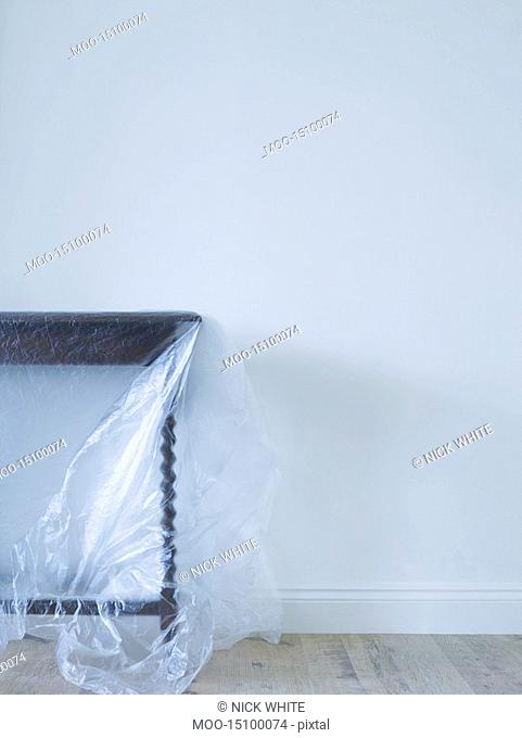 Table covered with plastic in empty room