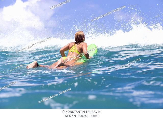 Indonesia, Bali, woman lying on surfboard in the ocean