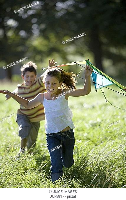 Brother and sister 7-10 playing with kite in field, boy chasing girl, smiling, front view