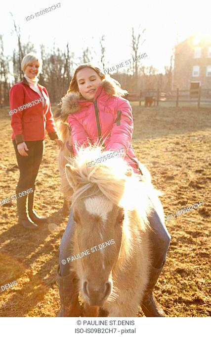 Young girl riding pony, mother watching from behind