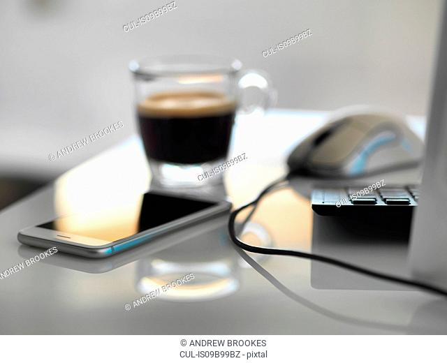 Morning coffee at office desk with mobile phone and computer