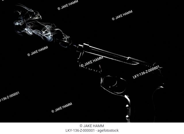 Silhouette of smoking gun against black background