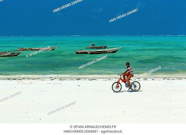Tanzania, Zanzibar, Jambiani, boy on a bicycle on the beach