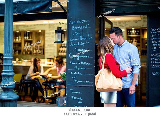 Romantic couple kissing outside cafe