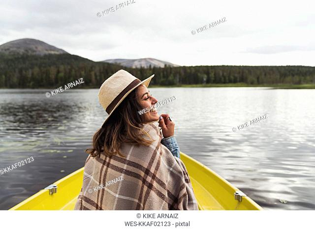 Finland, Lapland, happy woman wearing a hat on a boat on a lake