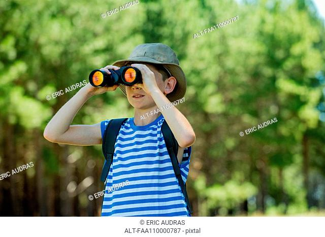Boy looking through binoculars outdoors