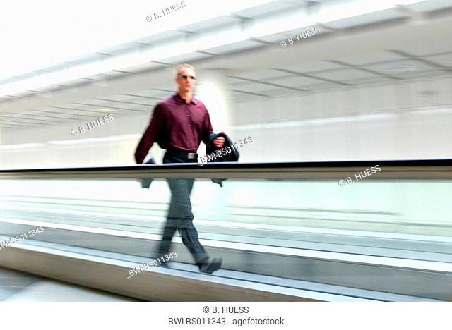 young businessman with sunglasses and briefcase hurrying on automatic walkway in airport
