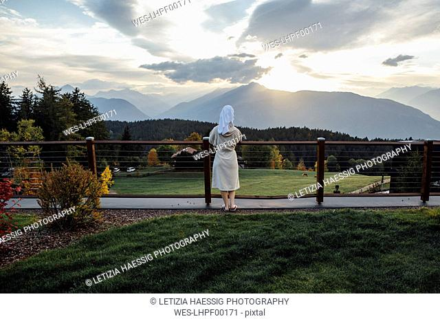 Woman waering bathrobe and turban standing at a fence looking at landscape