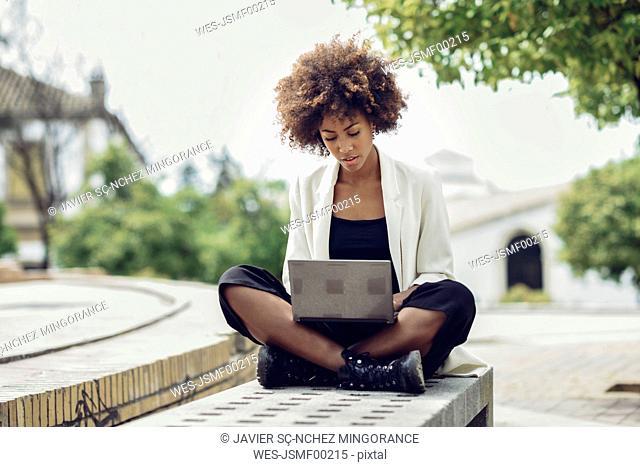 Fashionable young woman with curly hair sitting on bench using laptop
