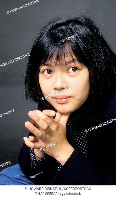 close up of asian girl with hands clasped and looking hopefully to our right
