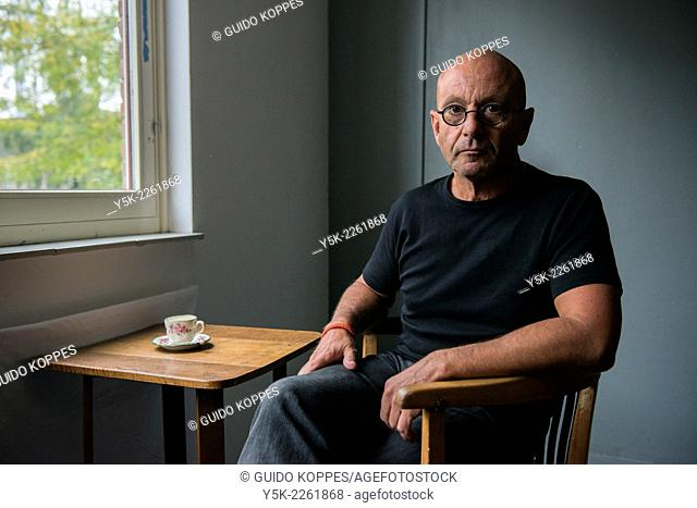 Tilburg, Netherlands. Portrait of a bald man wearing glasses, drinking a cup of coffee while sitting at a small table near the window