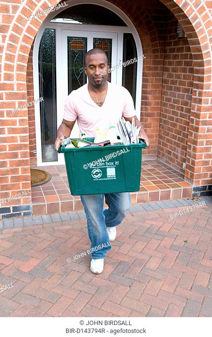 Man carrying curb side recycling collection box out of house onto pavement for collection