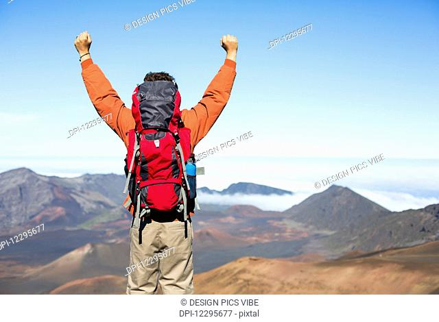 Hiker with backpack enjoying view from top of a mountain. Celebrating victory making it to the summit. Success and achievement concept