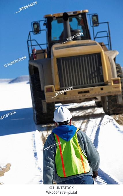 Engineer directing a front end loader at a construction site