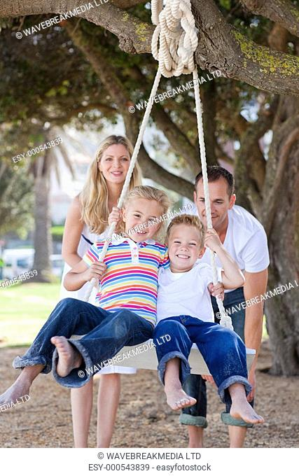 Joyful parents pushing their children on a swing in a park