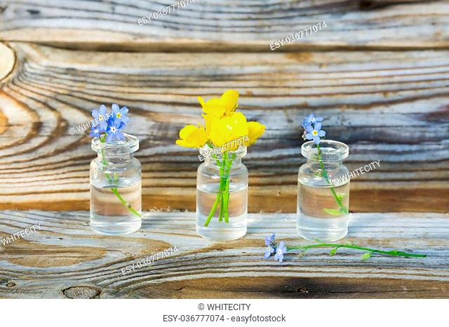buttercups and forget-me-nots in small glass jars