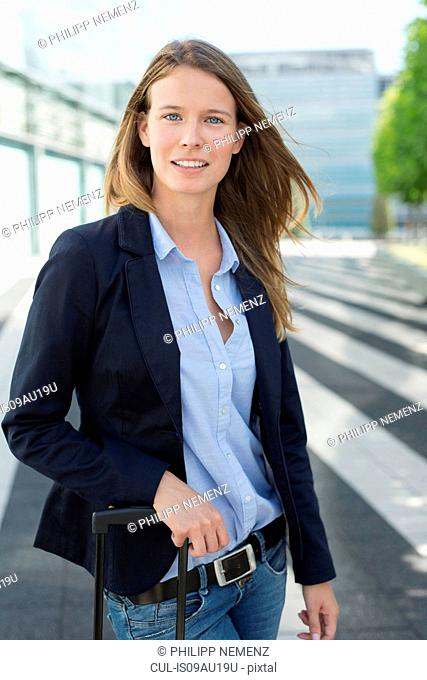 Portrait of young businesswoman with wheeled suitcase at airport