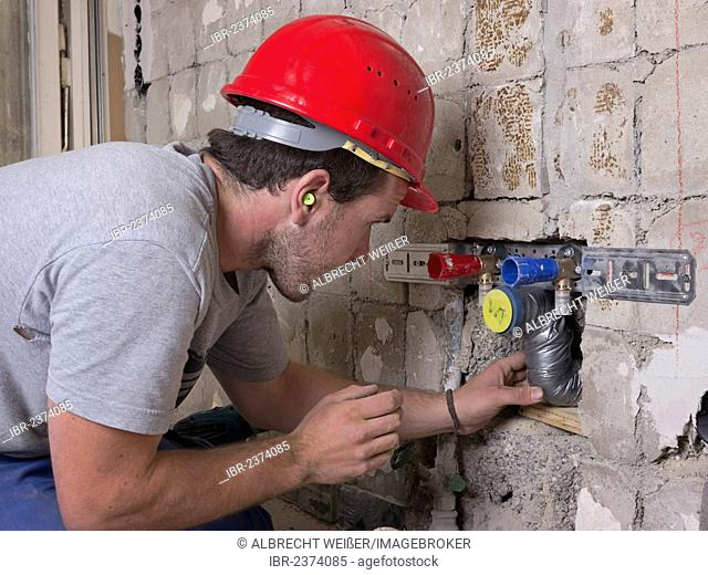 An electrician, systems mechanic for sanitary engineering, heating and air conditioning, installing a sewer pipe, refurbishment, Baden-Wuerttemberg, Germany