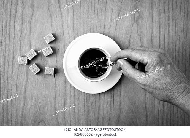 Cup of black coffee with sugar and hand mixing  Still Life  Zenital