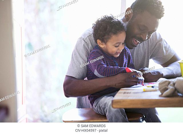 Happy father and toddler son coloring at table