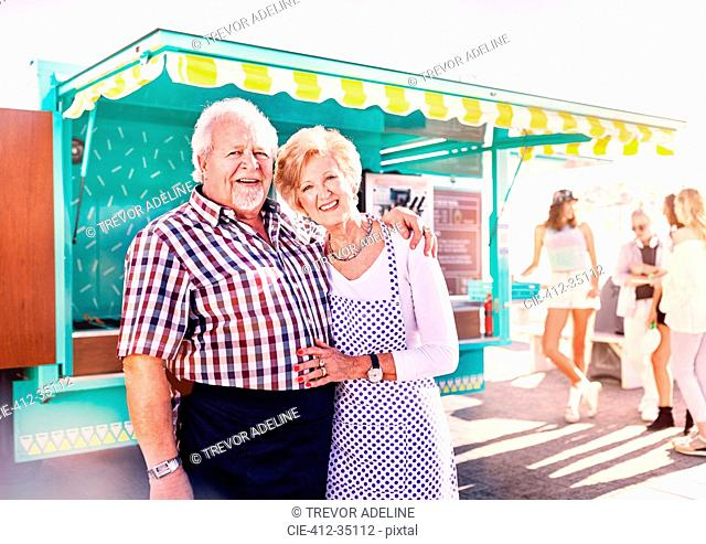 Portrait smiling senior business owners outside sunny food cart