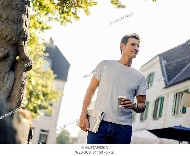 Mature man walking in he city with newspaper and digital tablet, drinking coffee