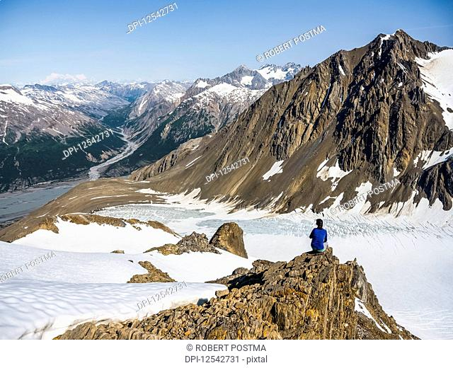 Woman enjoying an afternoon amongst the mountains and glaciers of Kluane National Park and Reserve; Haines Junction, Yukon, Canada