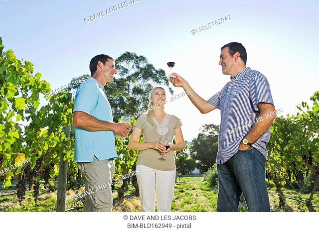 Caucasian friends tasting wine in vineyard