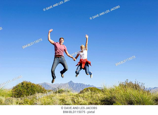 Caucasian couple jumping for joy on rural hilltop