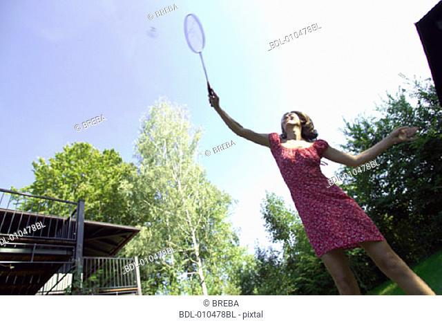 woman in garden playing badminton