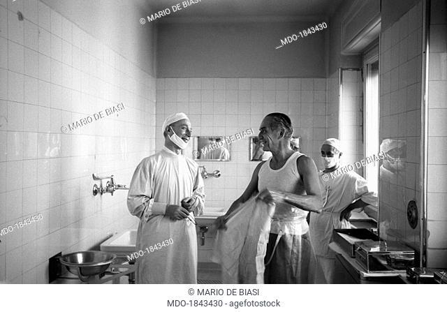 Italian heart surgeon Achille Dogliotti in vest smiling beside a colleague in a bathroom at the Molinette Hospital (University Hospital San Giovanni Battista)