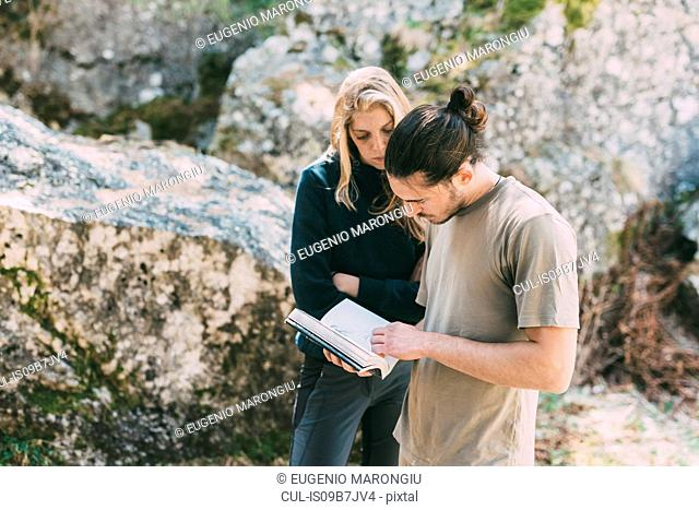 Male and female bouldering friends looking at guidebook, Lombardy, Italy