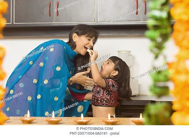 Side profile of a girl feeding a piece of burfi to her mother in a domestic kitchen